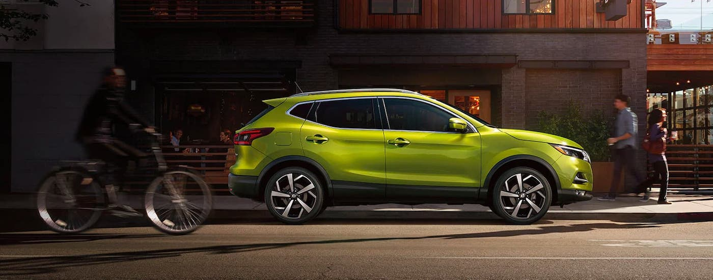 A lime green 2021 Nissan Rogue Sport is shown from the side while parked in front of a busy cafe after leaving a Nashville Nissan dealer.