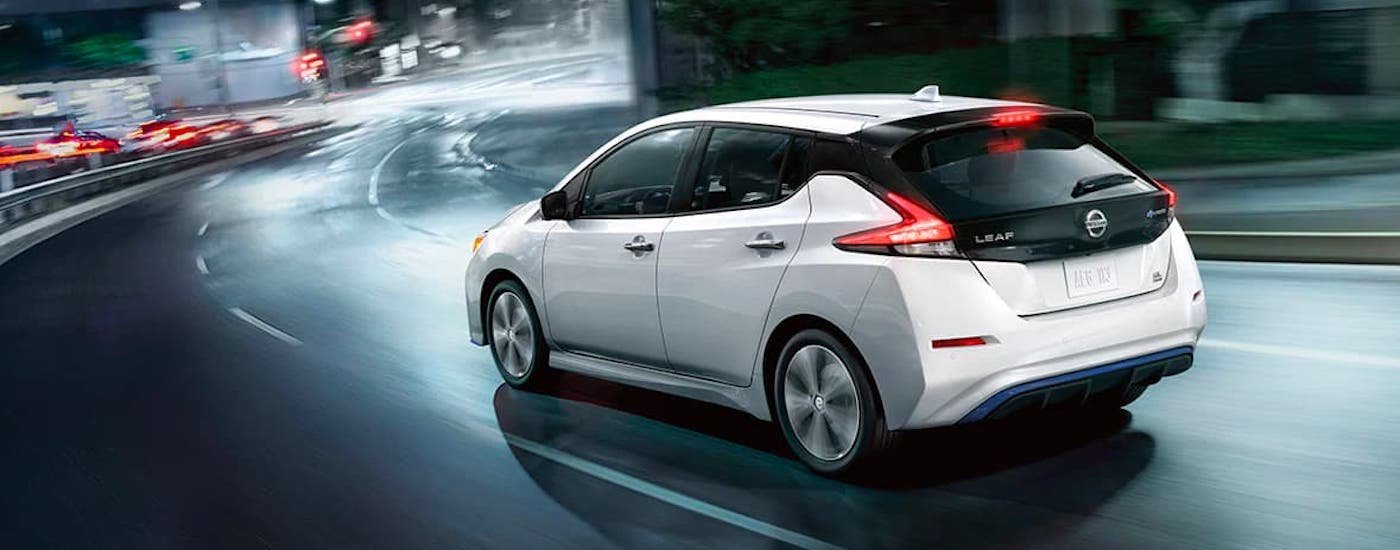 A white 2021 Nissan Leaf is shown from the rear and angled while driving on a highway at night.