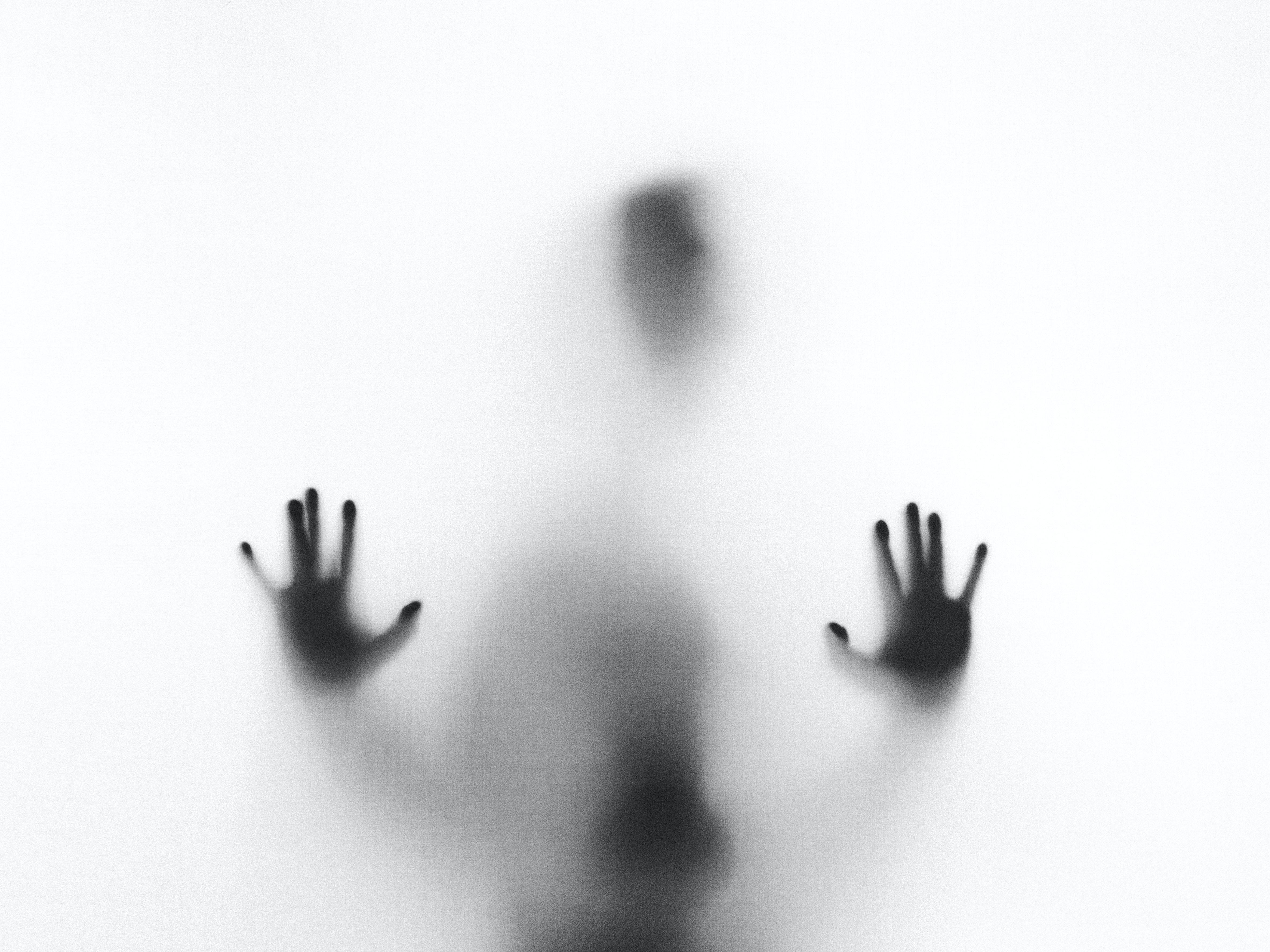 A person behind a fogged glass pane.