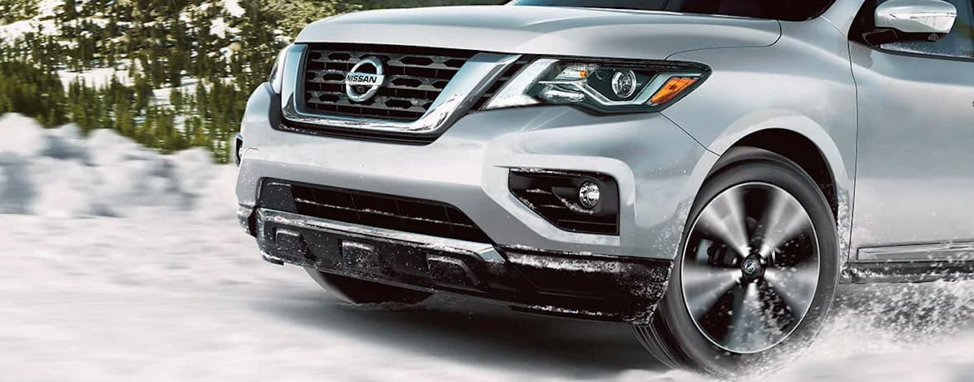 A closeup shows a wheel on a silver 2021 Nissan Pathfinder driving in snow.