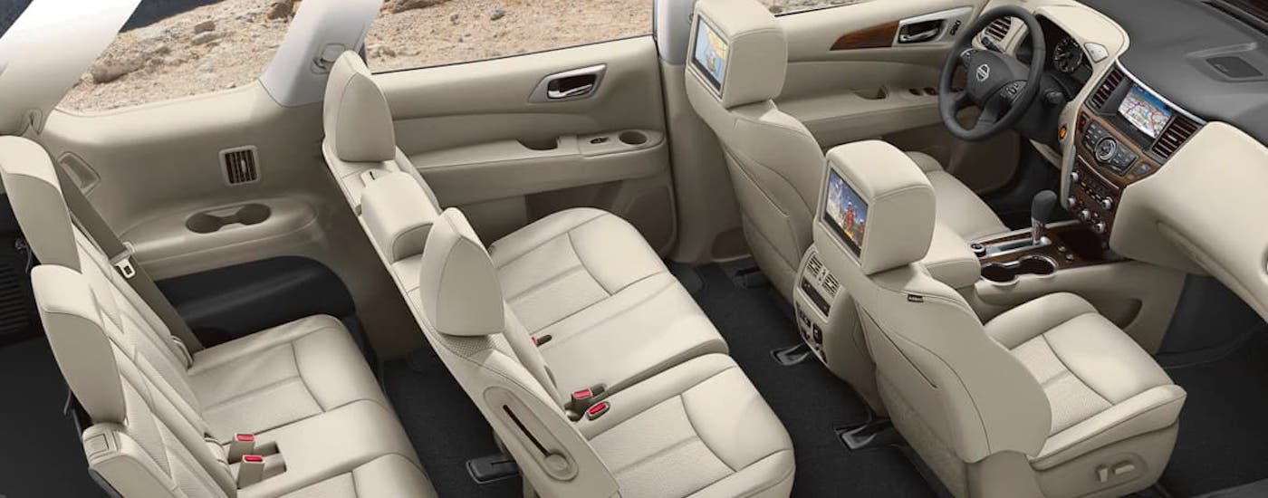 The three rows of tan-colored seats are shown in a 2021 Nissan Pathfinder from a high angle.