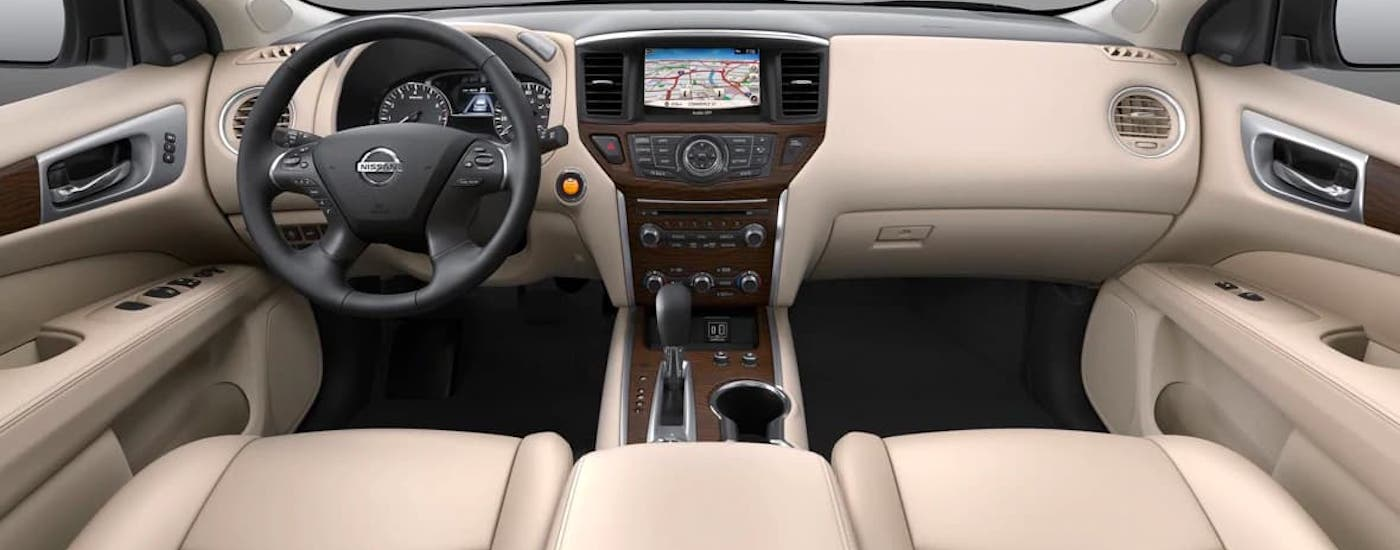 The tan dashboard and steering wheel of a 2021 Nissan Pathfinder are shown.