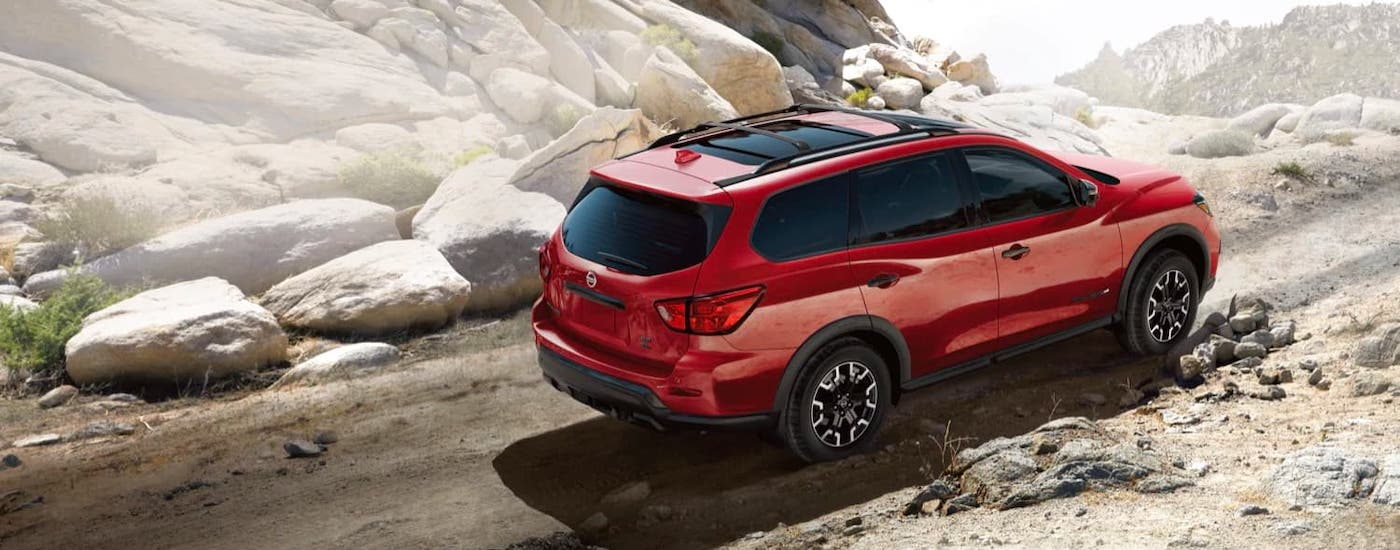 A red 2021 Nissan Pathfinder is driving on a dirt trail.