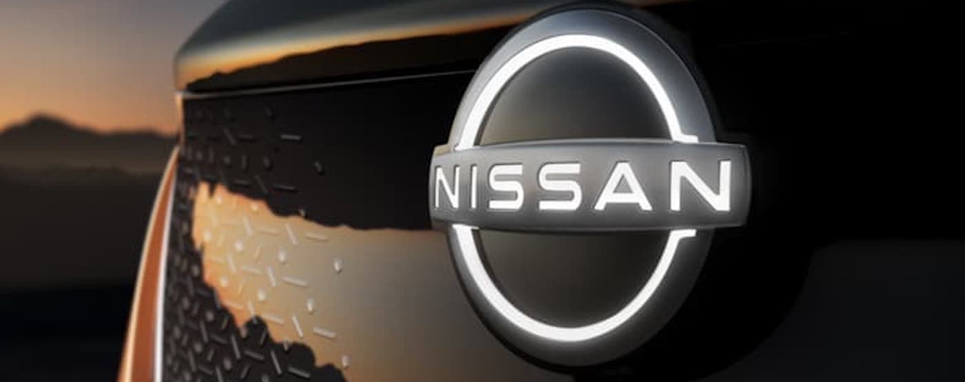 A closeup shows the illuminated Nissan badging on the grille of a copper-colored Nissan Ariya at sunset.
