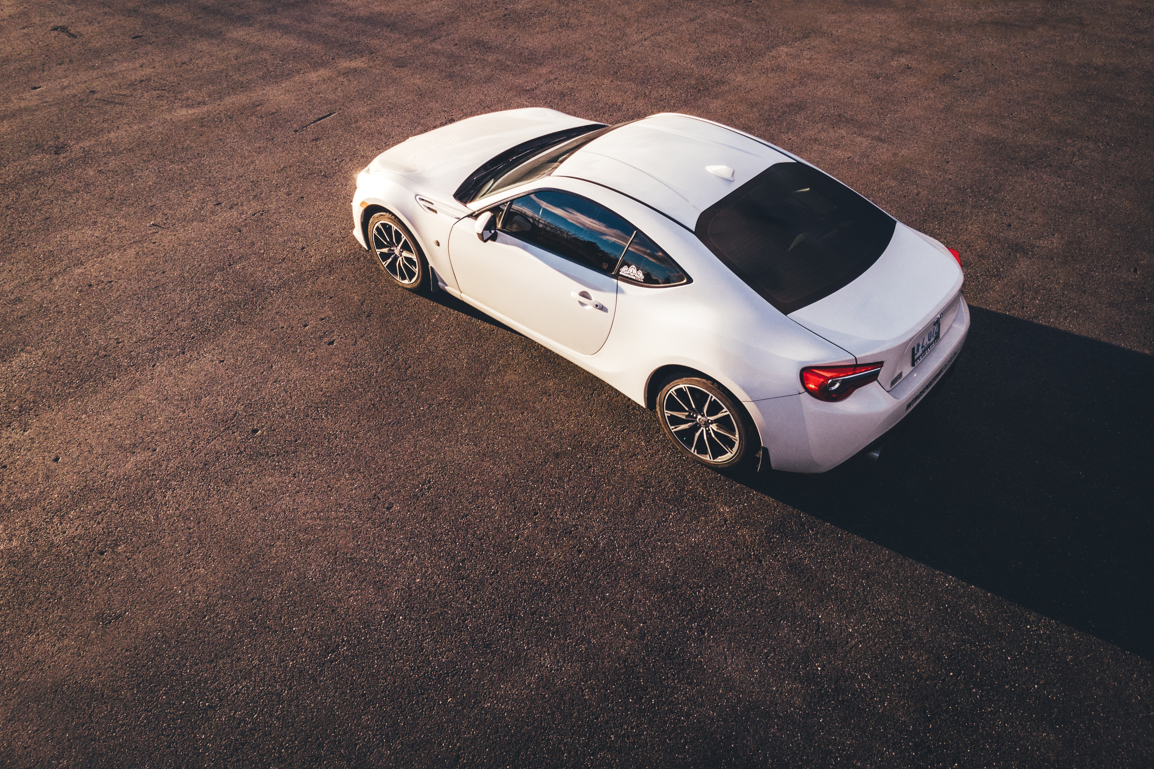 An overhead view of a stylsh white sports coupe.