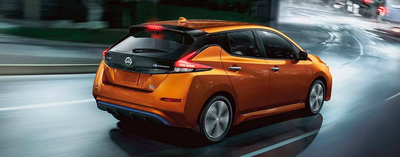 An orange 2021 Nissan LEAF is driving around a winding city street.
