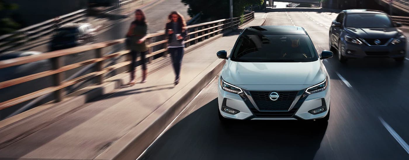 Women are walking next to a street where a white 2021 Nissan Sentra is shown driving from the front.