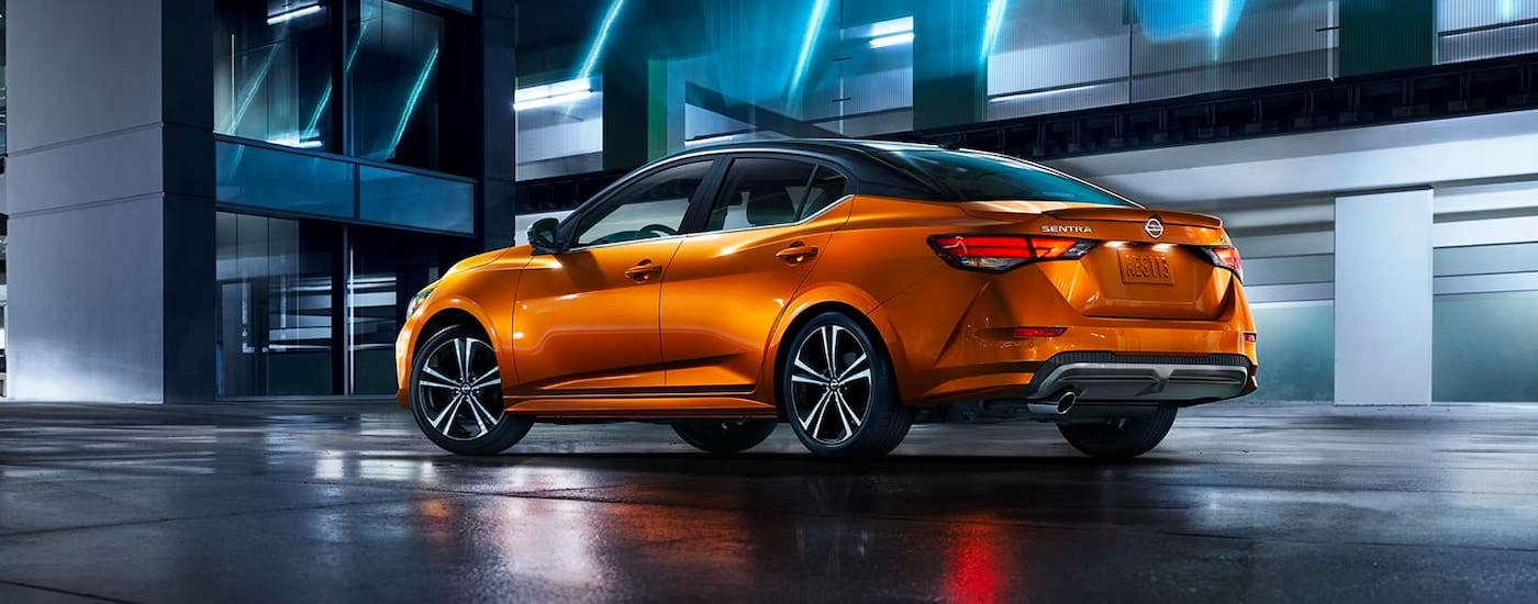 An orange 2021 Nissan Sentra is parked in front of a modern building with blue lights at night.