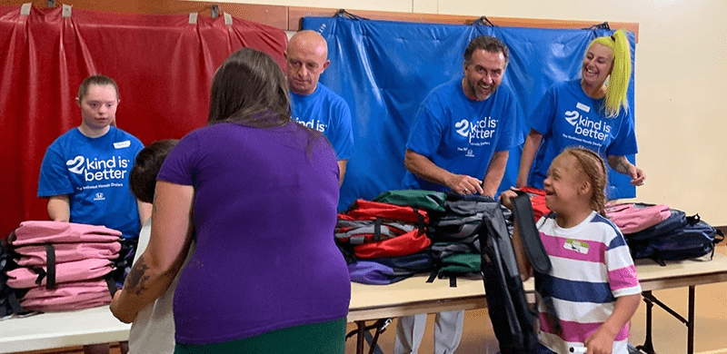 Photo of people passing out backpacks to children