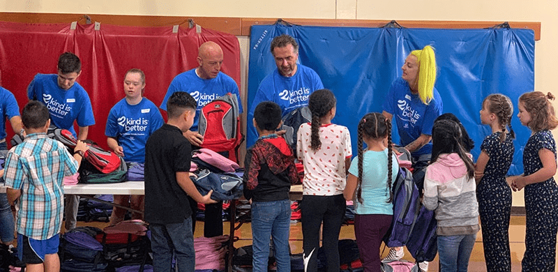 Kids smiling and picking out backpacks