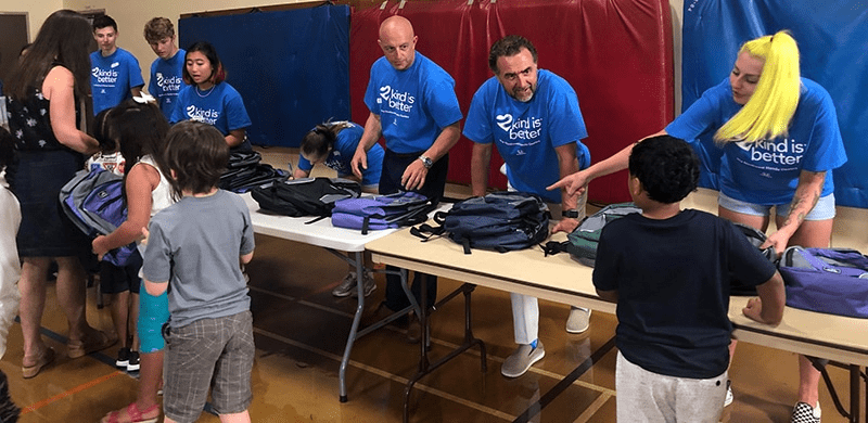 Excited workers helping kids pick out a backpack