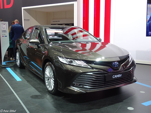 A black Toyota Camry Hybrid on a showroom floor at an automotive convention.
