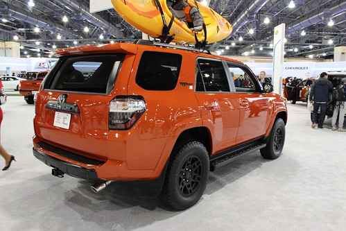 An orange Toyota 4Runner on a showroom floor with a yellow kayak strapped to the roof.