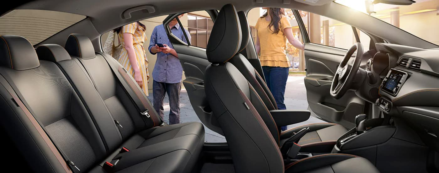 The grey interior of a 2021 Nissan Versa is shown with the doors open and people outside of it.