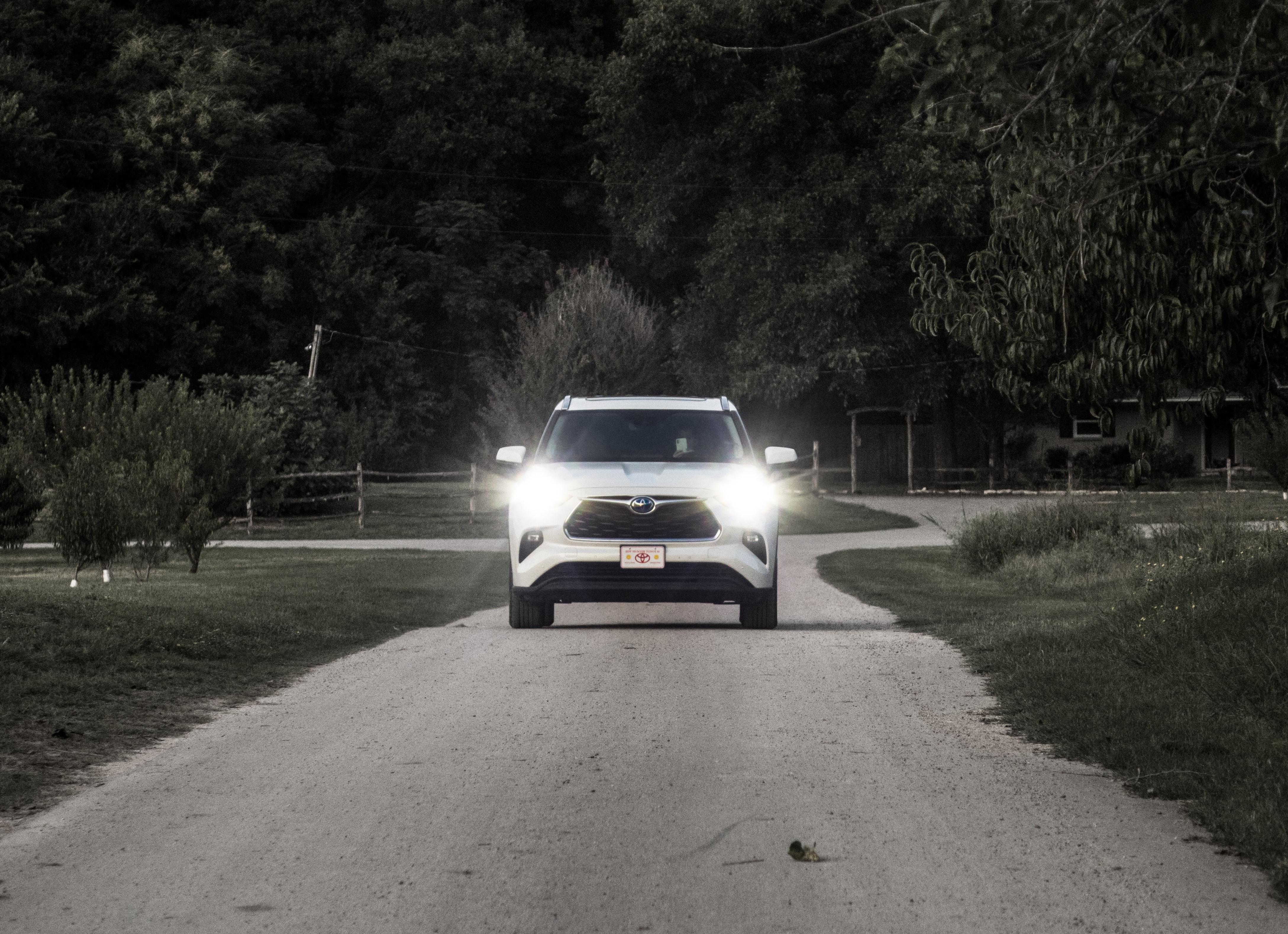 A white Toyota Highlander driving down a gray asphalt farm road.