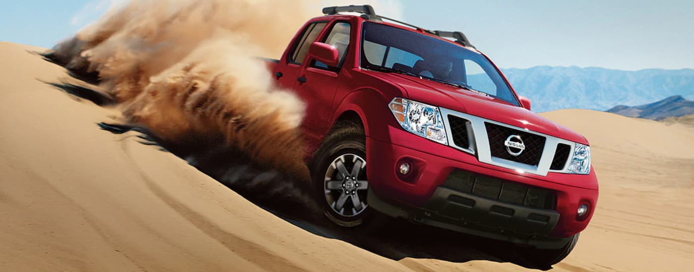 A red 2021 Nissan Frontier is off-roading in sand.