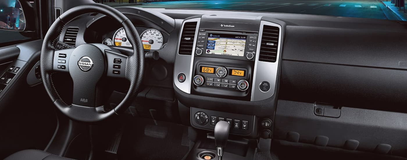 The black interior of a 2021 Nissan Frontier is shown facing the dashboard.