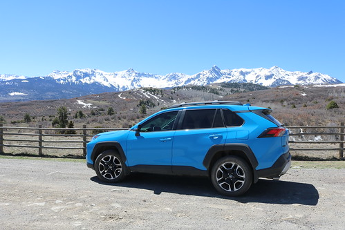 A Toyota RAV4 parked on the side of the road in front of a snow topped mountain.