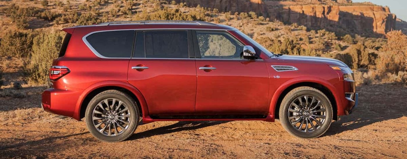 A red 2021 Nissan Armada is shown from the side in front of rock formations.