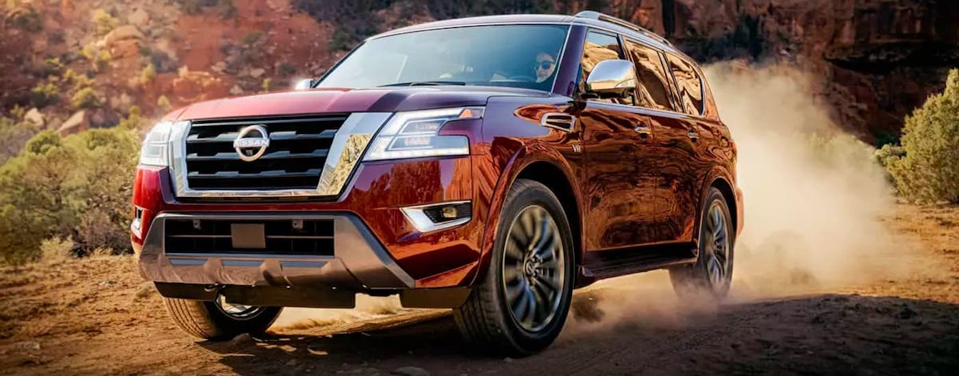 A red 2021 Nissan Armada is kicking up dirt while off-roading.
