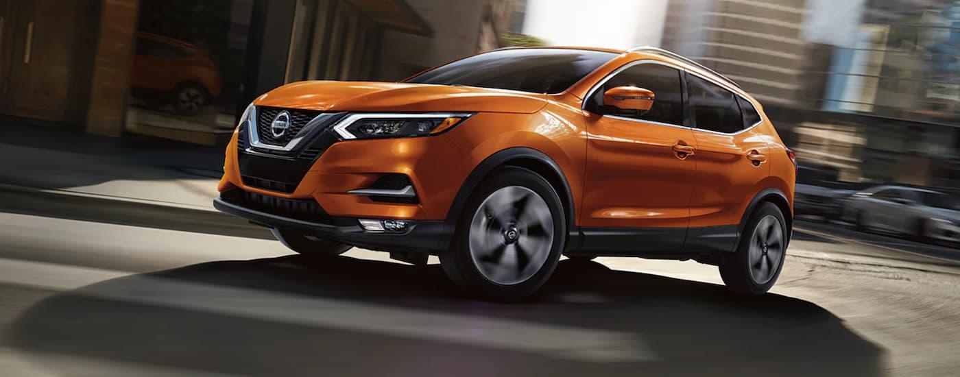 An orange 2021 Nissan Rogue Sport is driving on a city street.