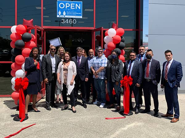 group of people cutting ribbon with big scissors