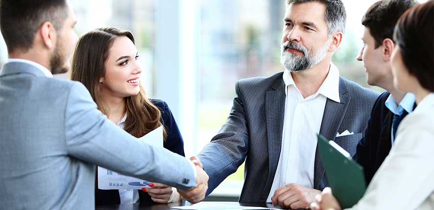 Couple shaking hands with Sales Person